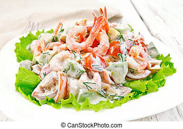 Salad with shrimp and avocado in white plate on board