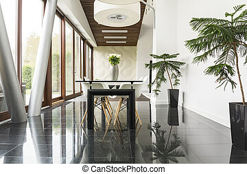 Minimalist dining room with black floor, white wall and...