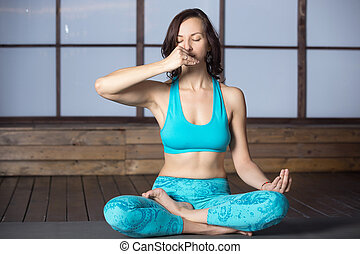 Young attractive woman making Alternate Nostril Breathing,...