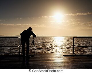 Man photograph with camera on tripod. Tourist at handrail on...
