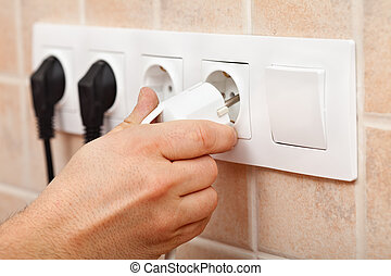 Hand plugging a power cord into electrical wall fixture -...