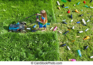 Pollution concept with little girl using plastic lawn mower