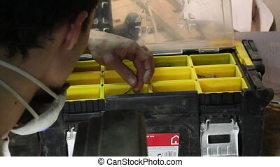 young craftman looks for proper pintle in yellow instrument...