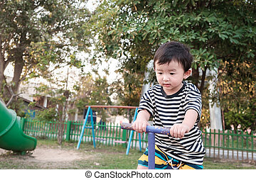 Happy kid play teeter totter in playground, color tone,...