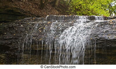 Waterfall Brink Loop - Water plunges over a rocky cliff in...
