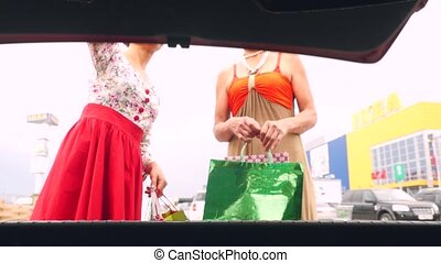 Young happy women putting shopping bags into car trunk at shopping mall outdoor. Mum and her daughter have a shopping time. 3840x2160