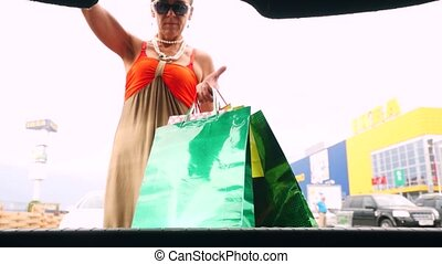 Mature smiles woman in age putting shopping bags into car...