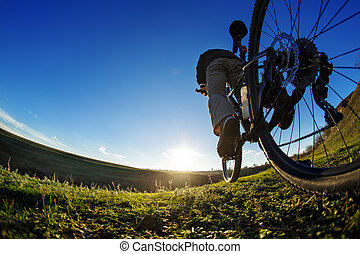 Man on mountain bike rides on the trail on a beautiful...