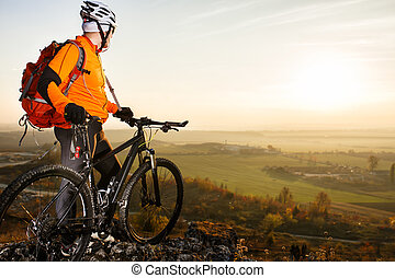 Man with the bike standing on a rock. spring nature. Cyclist...