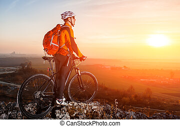 Cyclist leaning against bicycle in front of scenic skyline view of sunset.