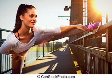 young woman streching before sports. urban sport style -...