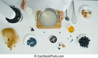 Chef pours milk into a bowl