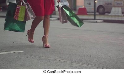 Shopaholic woman in beautiful dress holding many shopping bags walking on the street in slowmotion. 1920x1080