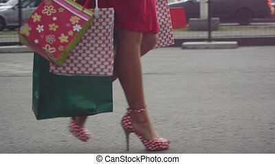 Shopaholic woman in beautiful dress holding many shopping...