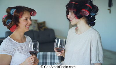 Two happy women friends with funny curler hairstyle drink wine and talk at home