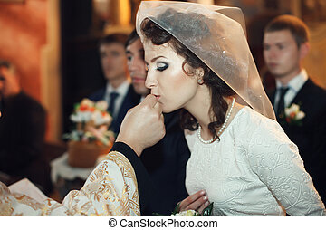 Classy bride kisses a wedding ring held by a priest