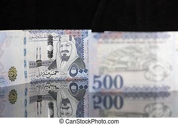 New Saudi Riyal notes on a dark reflective surface - Saudi...