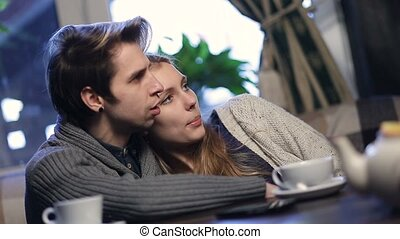 Loving young couple hugging while resting in cafe