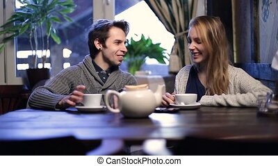 Loving couple on a date drinking tea at restaurant - Smiling...