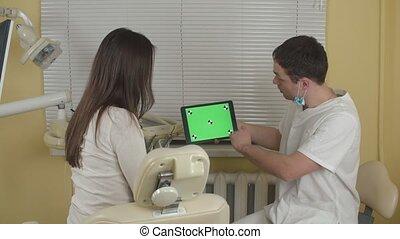 Dentist explaining procedure to female patient in dentist...
