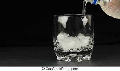 Mineral water in the glass with ice cubes