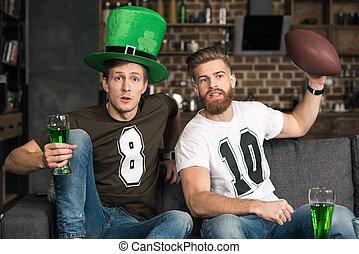 men watching football match - Emotional young men watching...