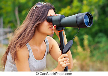 Positive girl watching in Spyglass while walking