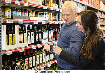 Couple Using Smart Watch In Grocery Store - Mature couple...
