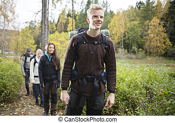 Smiling Man With Friends Hiking On Forest Trail