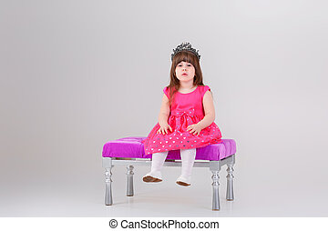 beautiful little girl in pink Princess dress with crown sitting