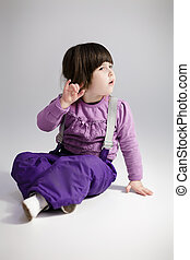 little cute girl in purple clothes trying to hear on grey...