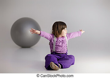 little girl in purple clothes with arms outstretched and big...