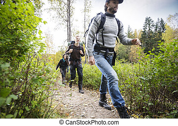 Young Man With Friends Hiking On Forest Trail