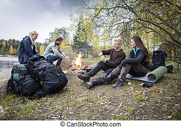 Friends Enjoying Camping On Lakeshore - Multiethnic male and...