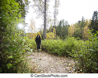 Young Female Hiker Walking On Forest Trail - Full length of...
