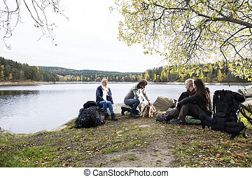 Friends Looking At Man Preparing Bonfire On Lakeside Camping...