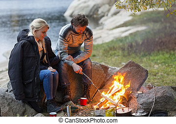 Couple Sitting By Campfire On Lakeshore - Full length of...