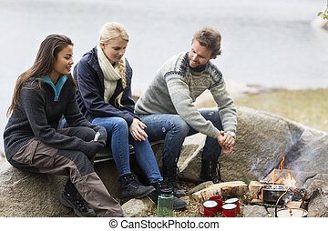 Friends Talking While Sitting On Rock During Camping