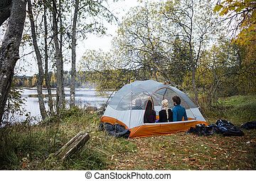 Friends Relaxing In Tent On Lakeshore - Multiethnic young...