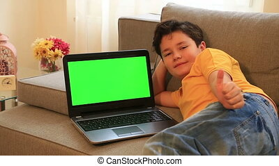 Young boy with green screen laptop monitor - Child...