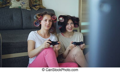 Two funny women play console games with gamepad and have fun at home