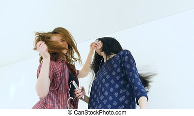 Slow motion of young happy women friends dancing over a bed with earphones and have fun