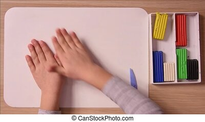 The child rolls a ball of plasticine hand on the board for modeling, close-up, top view