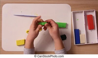 Baby rolls his hands a small piece of plasticine and...