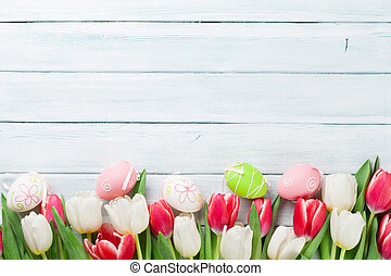 Easter eggs and colorful tulips on wooden background. Top...
