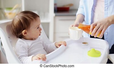 happy mother with spoon feeding baby at home