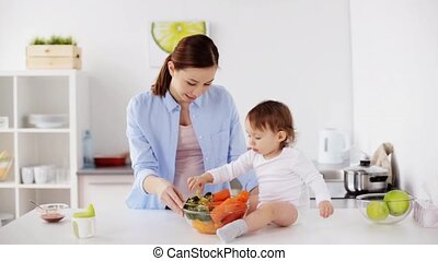 mother and baby with vegetables at home kitchen - family,...