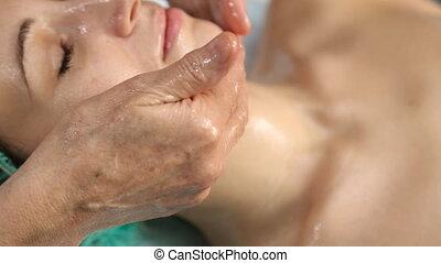 Woman doing facial massage - cosmetologist doing facial...