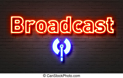 Broadcast neon sign on brick wall background.