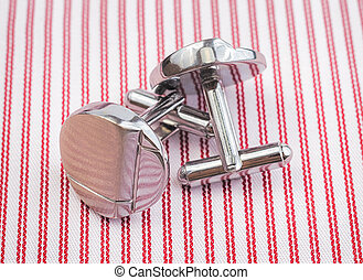 Silver cuff links on striped red background close up.